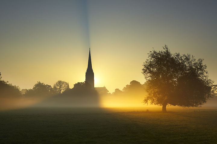 A misty dawn with the sun rising behind Salisbury Cathedral, Wiltshire, England.