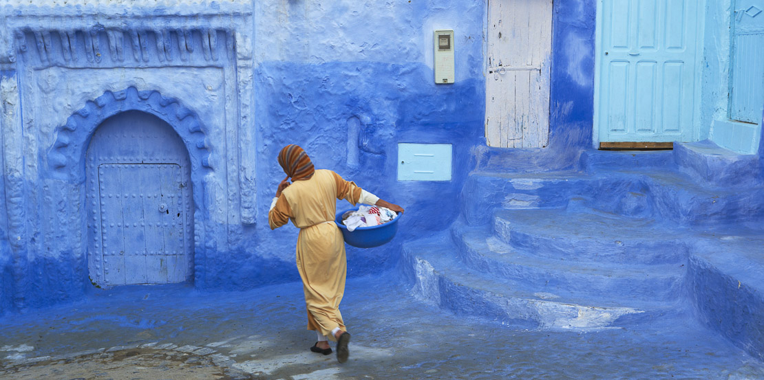 a woman with her washing in the blue walled town of Chefchaouen, Morocco