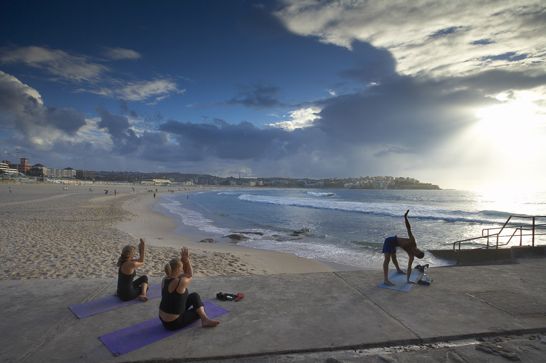 women and man doing exercises on Bondi Beach at dawn, Sydney, New South Wales, Australia
