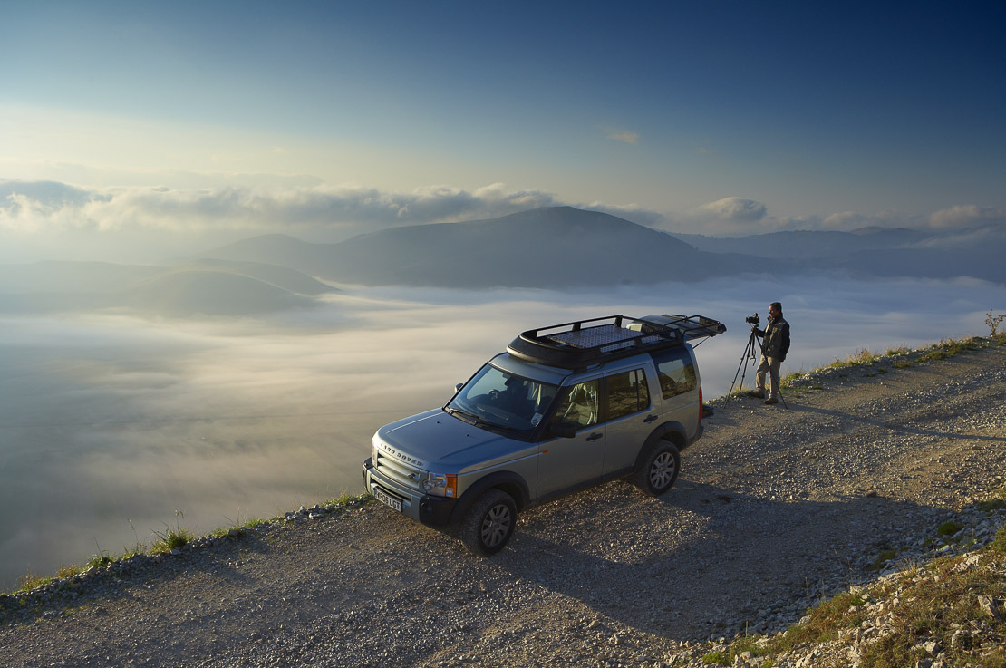 a photographer working beside a 4x4 vehicle (Land Rover) above the mist lying on the Piano Grande at dawn, Monti Sibillini National Park, Umbria, Italy. (MR)
