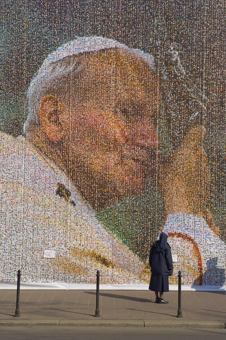a nun looking at a huge collage of Pope John Paul II, Krakow (Cracow), Poland. (NR)