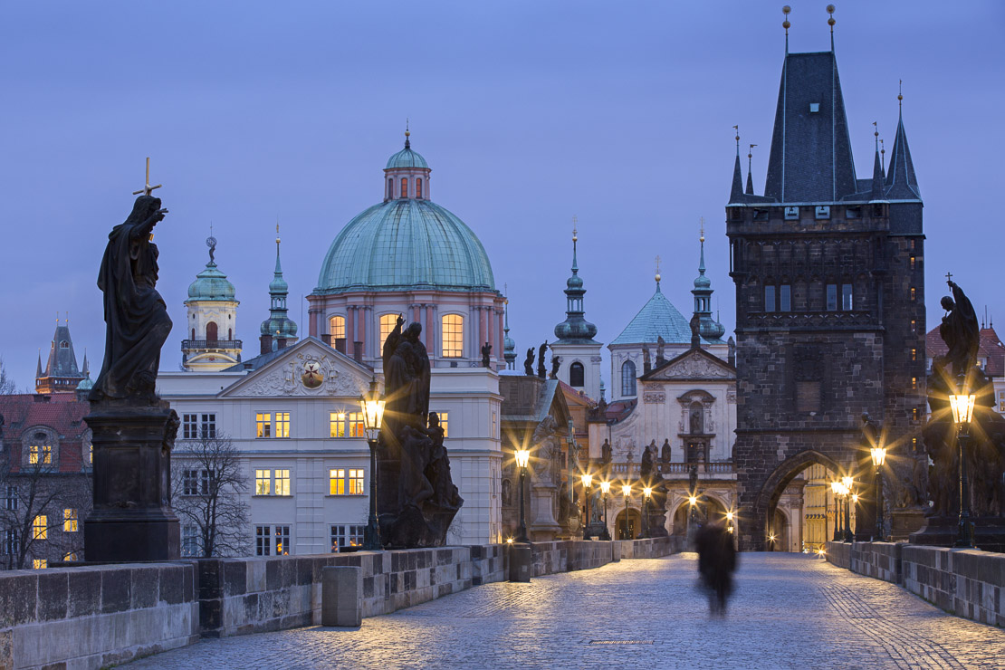 a solitary figure on the Charles Bridge at dawn with the towers and spires of the Old Town beyond, Prague, Czech Republic