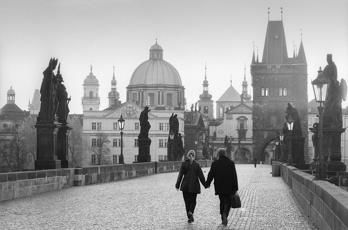 couple walking on the Charles Bridge at dawn, Prague, Czech Republic