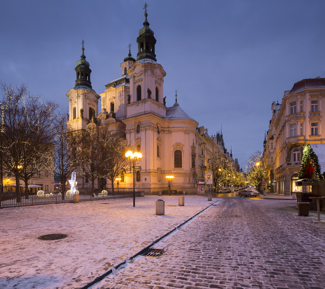 the Church of St Nicholas with a smattering of snow and Chrstmas lights in the Old Town Square, Prague, Czech Republic