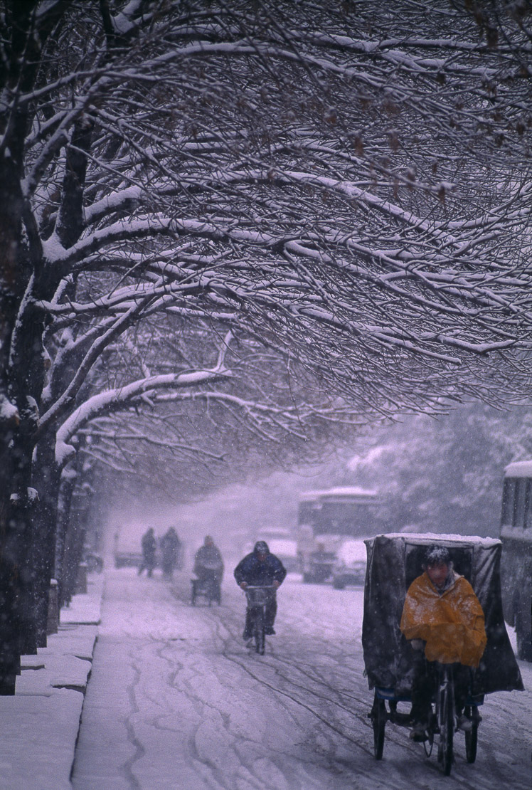 bicycles and rickshaws in winter in heavy snowfall, street scene, Beijing, China