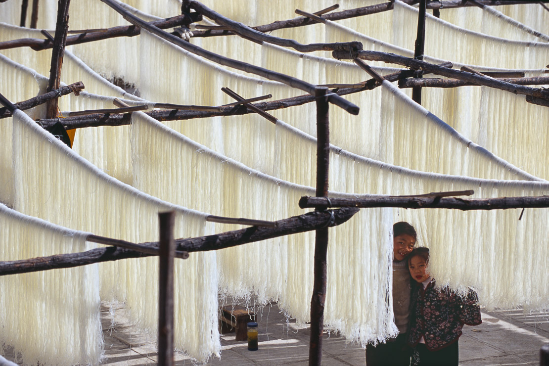 fresh noodle drying in open field with children, Dali, Yunnan Province, China