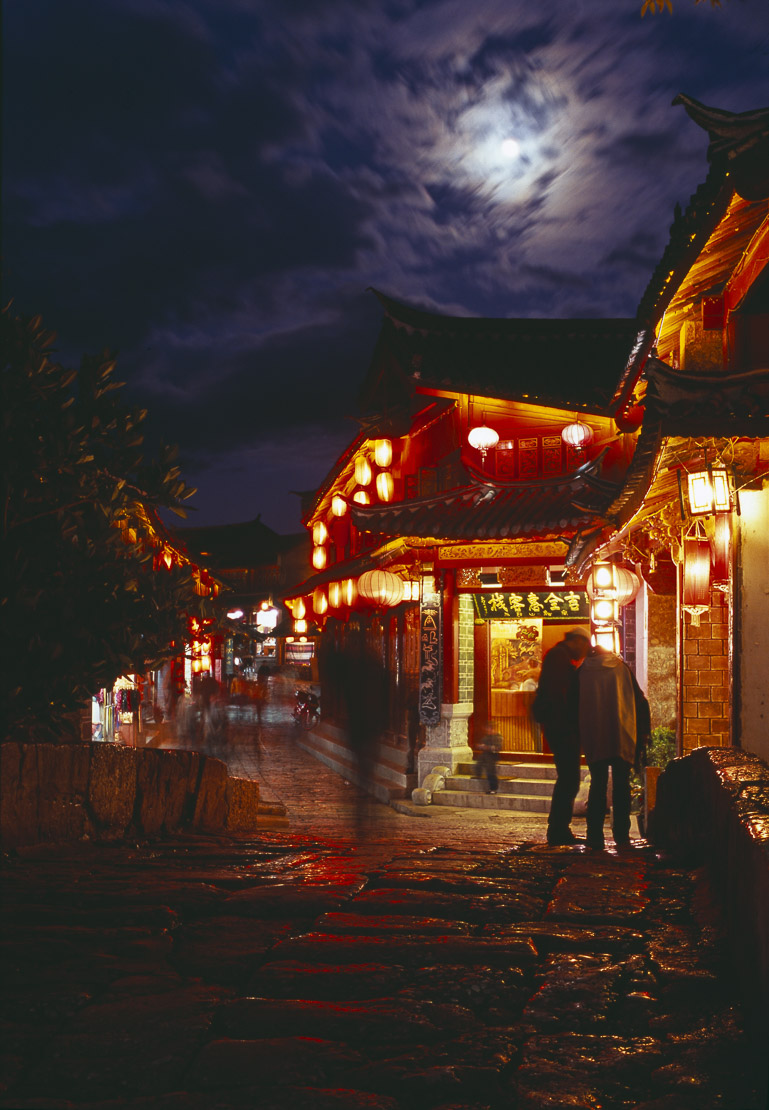 cobblied street and stream in Lijiang at dusk, Lijiang, Yunnan Province, China