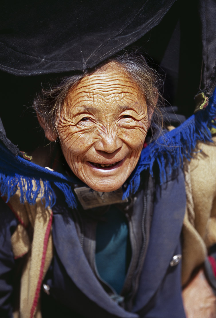 elderly woman carrying bundle of wood, Yunnan Province, China