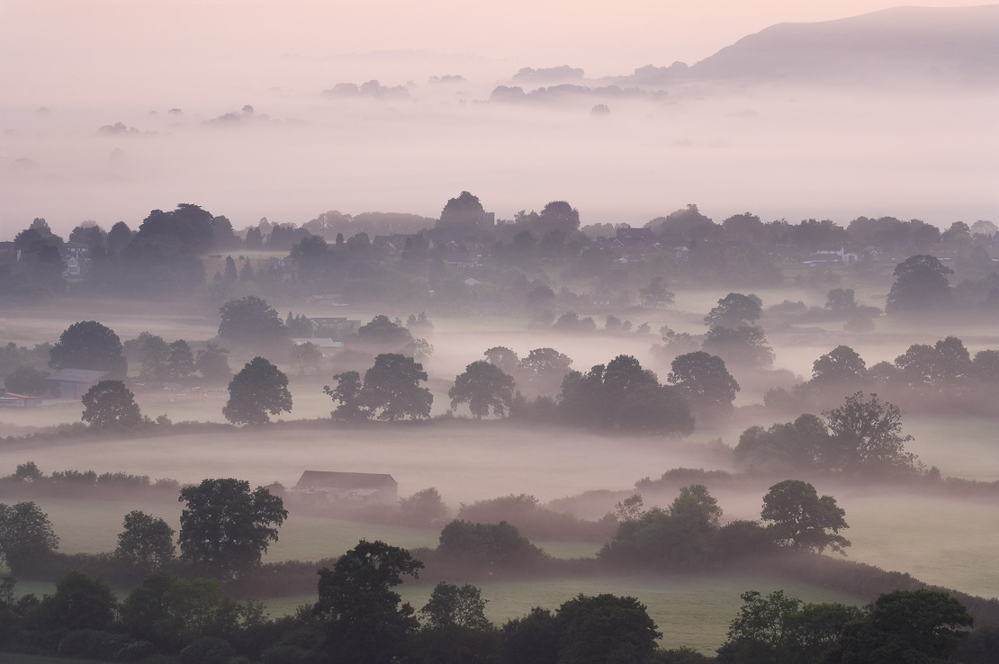a misty dawn in the Blackmore Vale from Bulbarrow Hill, nr Okeford Fitzpaine, Dorset, England, UK