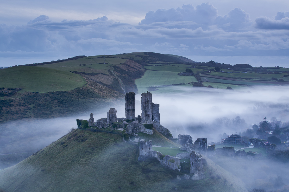 Corfe Castle in the mist at dawn, Dorset, England, UK