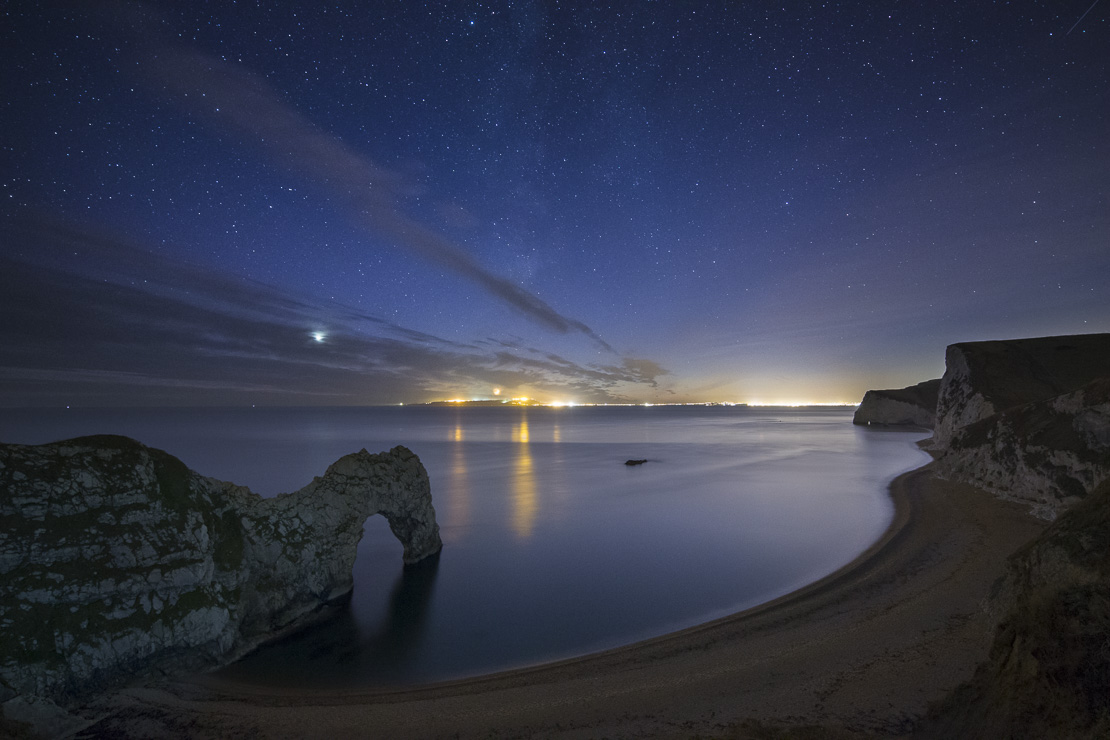 the stars and Milky Way over Durdle Door and the Jurassic Coast, with the lights of Weymouth & Portland beyond, Dorset, England