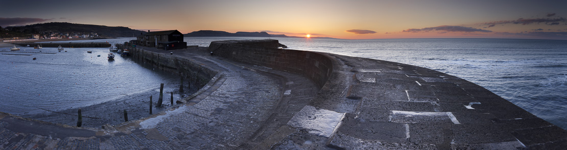 the Cob at Lyme Regis at dawn with the Jurassic Coast beyond, Dorset, England, UK