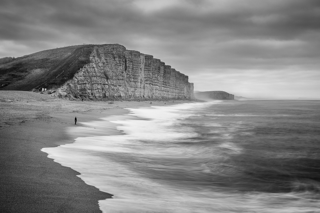 Waves breaking on the beach beneath East Cliff, West Bay, Jurassic Coast, Dorset, England, UK