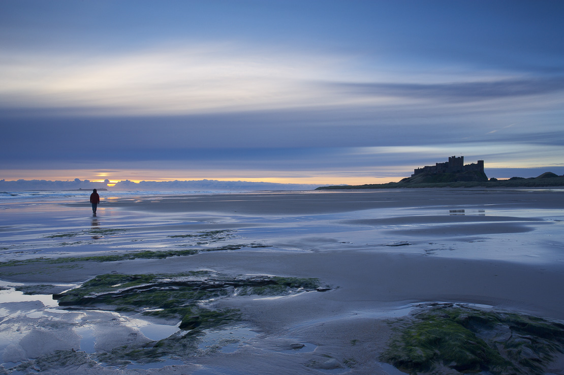 solitary figure on the beach at dawn, Bamburgh Castle, Northumbria, England, UK