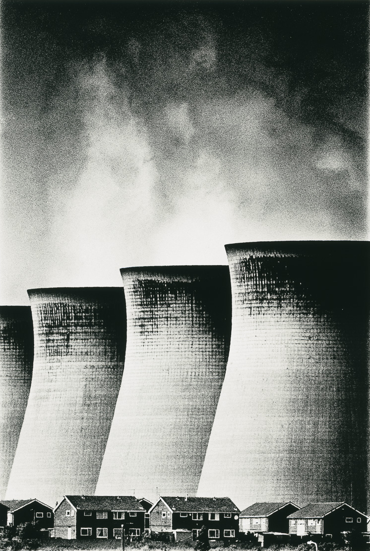 the belching cooling towers dwarfing the domestic houses at Ferrybridge Power station, Yorkshire, England, UK