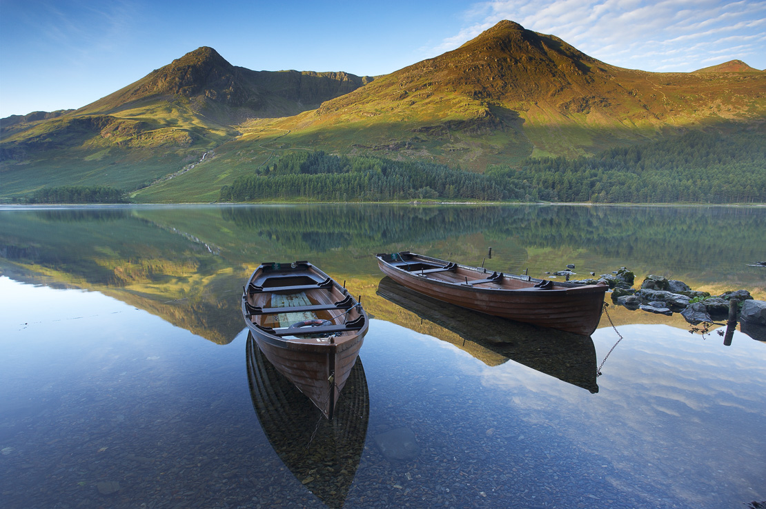 boats on the shore of Buttermere at dawn, Cumbria, Lakes District, Cumbria, England, UK