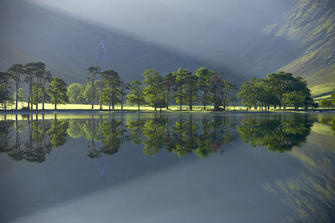 reflections on the shore of Buttermere at dawn, Cumbria, Lakes District, Cumbria, England, UK