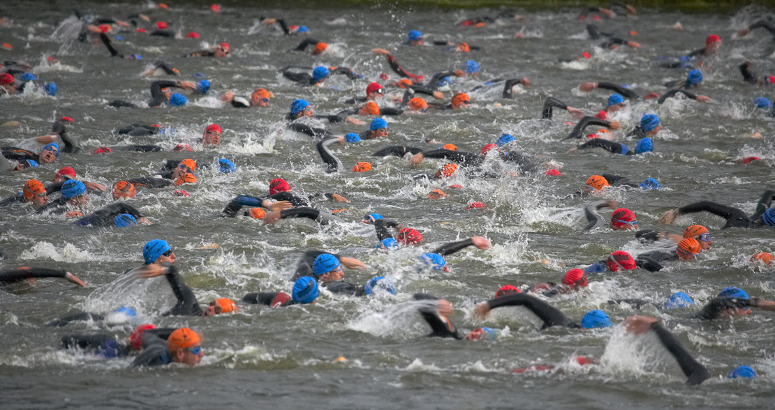 tri-athletes competing in the swimming phase of the Ironman Triathlon at Sherborne Castle, Dorset, UK. (NR)