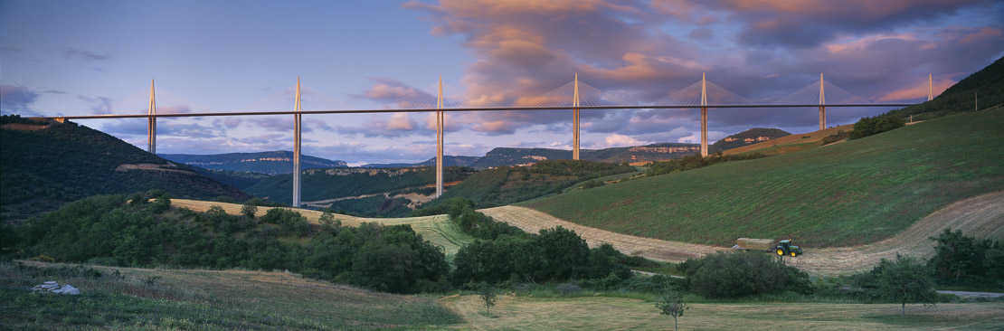 the Viaduc de Millau spanning the Gorge du Tarn with tractor working in the fields, Aveyron, Midi-Pyrénées, France