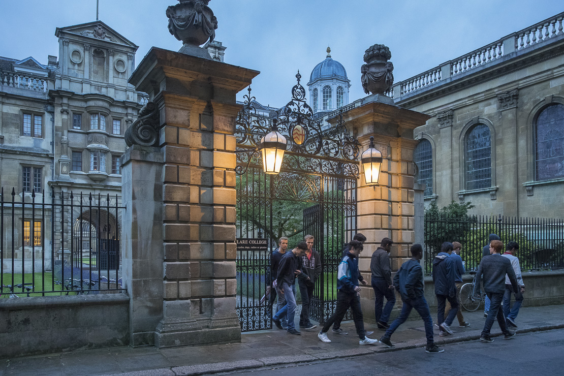 Students leaving Clare College, Cambridge at dusk, England, UK
