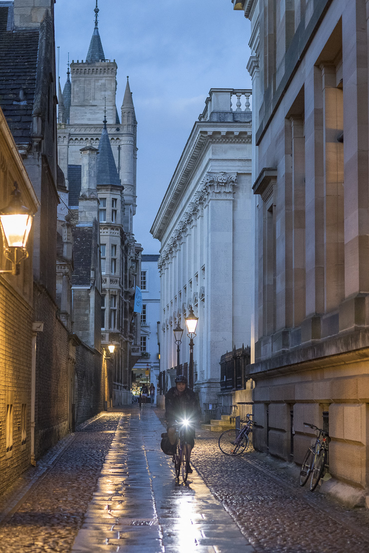 A student cyclist on Senate House Passage at dusk, Cambridge, England, UK