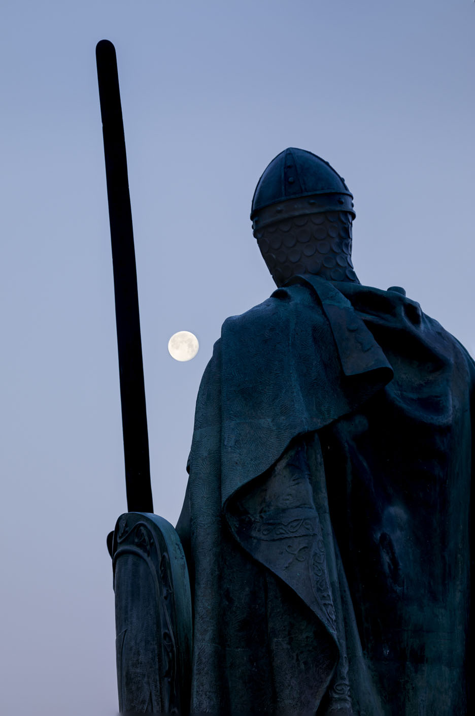 The full moon and statue of King Afonso I in front of the Castle, Guimarães, Braga, Portugal