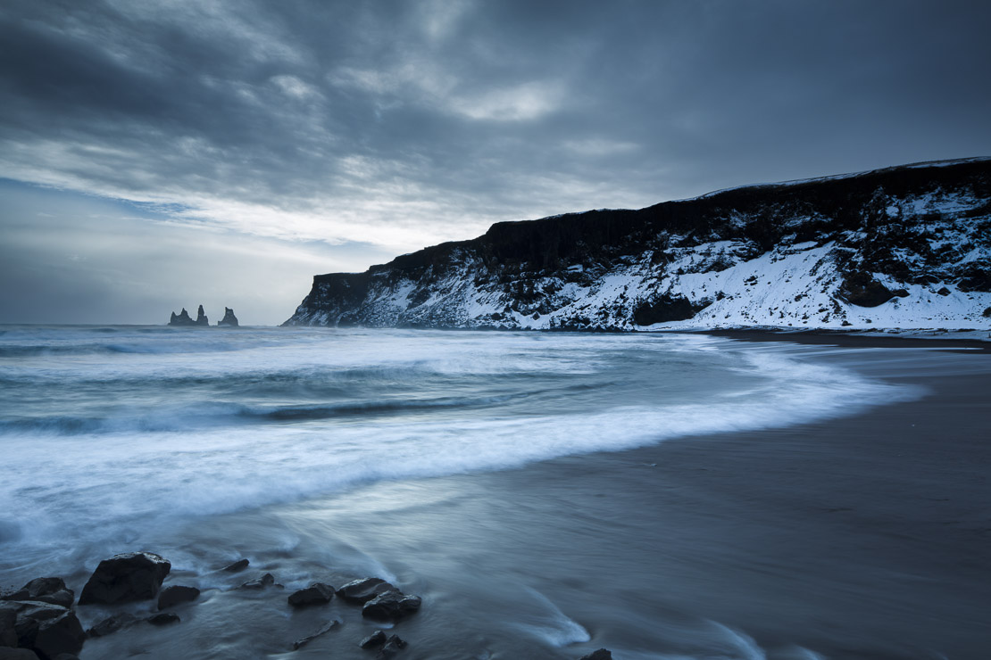 the black sand beach at Vík í Mýrdal in winter, with the Renisdrangar basalt sea stacks beyond, southern Iceland