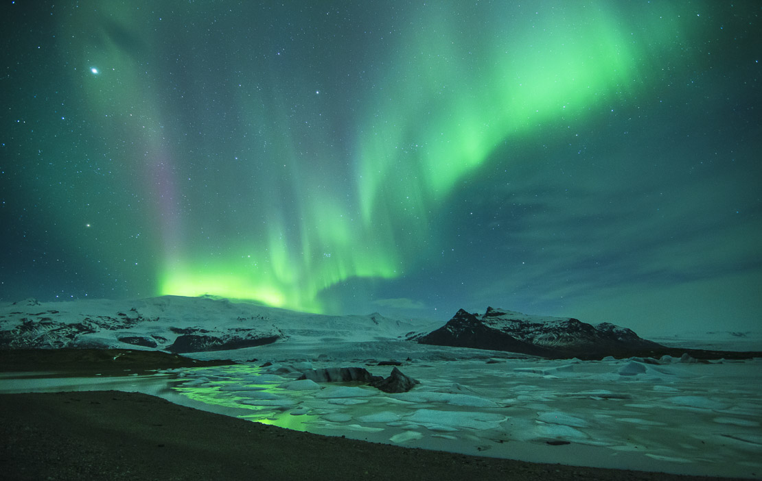 the Northern Lights (Aurora Borealis) over the Vatnajokull galcier and Fjallsarlon, eastern Iceland