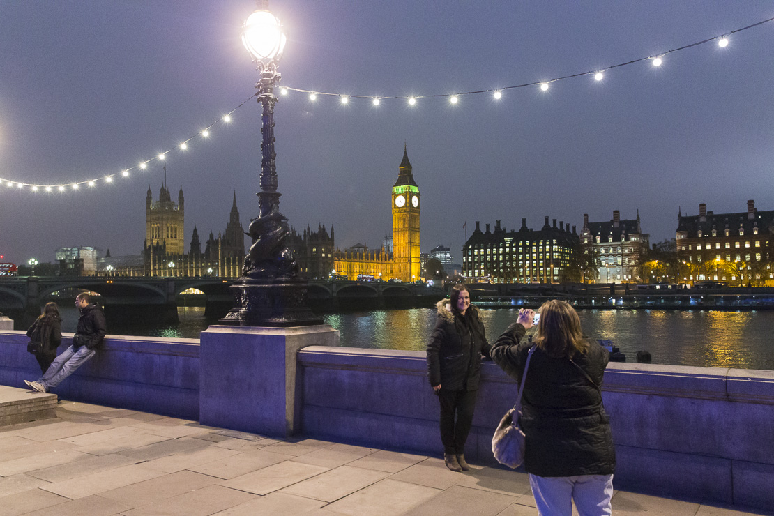 a woman taking a picture on the Embankment at dusk with Westminster Bridge and the Palace of Westminster beyond, London, England, UK