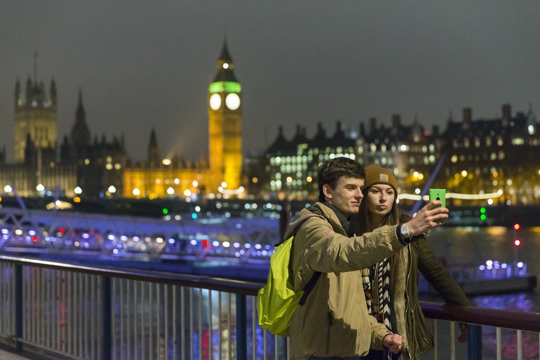 a man and a woman taking a slefie on the Embankment at dusk with Westminster Bridge and the Palace of Westminster beyond, London, England, UK