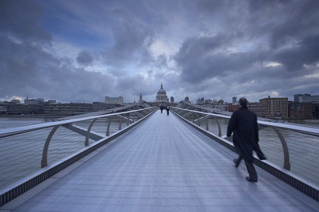 commuter on the Millennium Bridge over the River Thames with St Paul's on the skyline beyond, London, England, UK