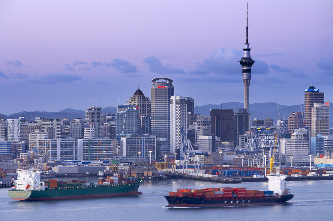 the City Centre with the Skytower, waterfront & docks with two container cargo ships, Auckland, New Zealand. (NR)
