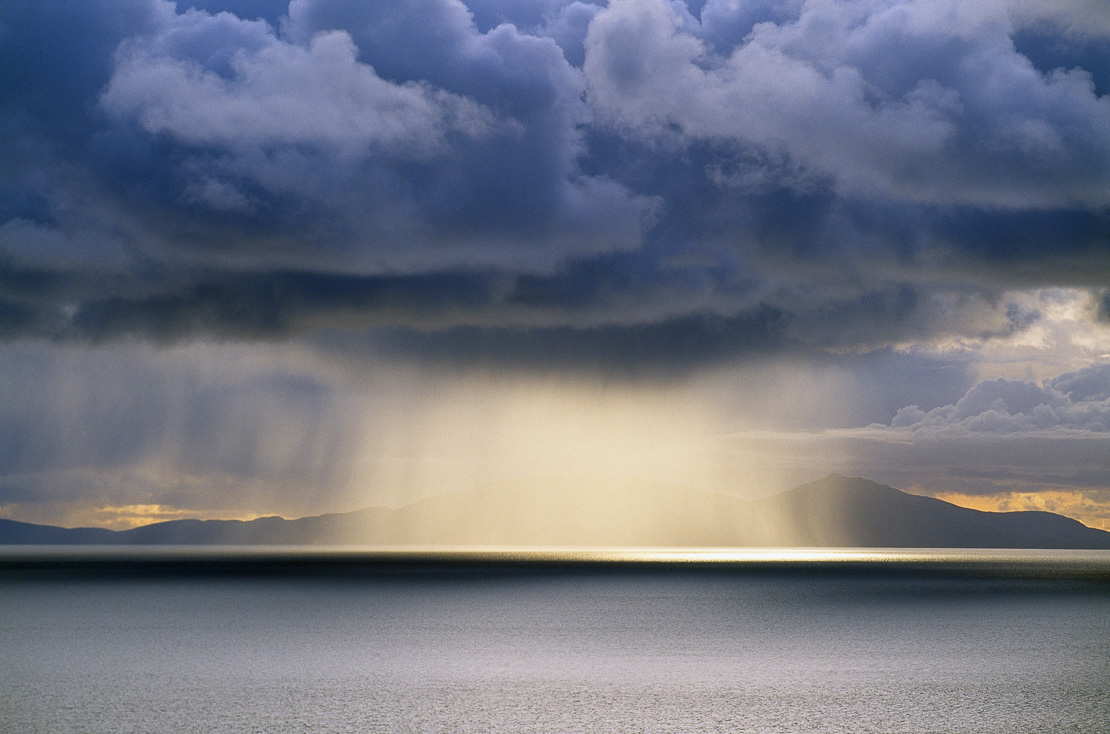 a shower crossing North Uist with Eaval disappearing in the rain (taken from Neist Point) Isle of Skye, Scotland, UK