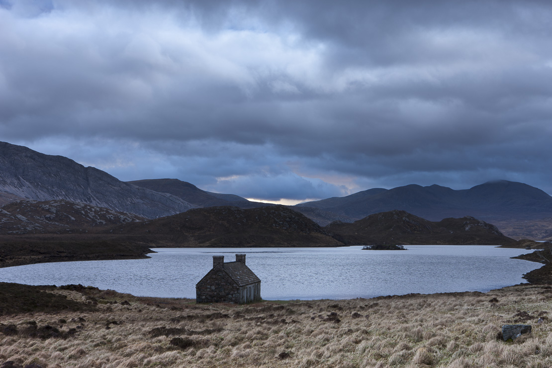 an abandoned crofters cottage by a lochan in Sutherland, Scotland