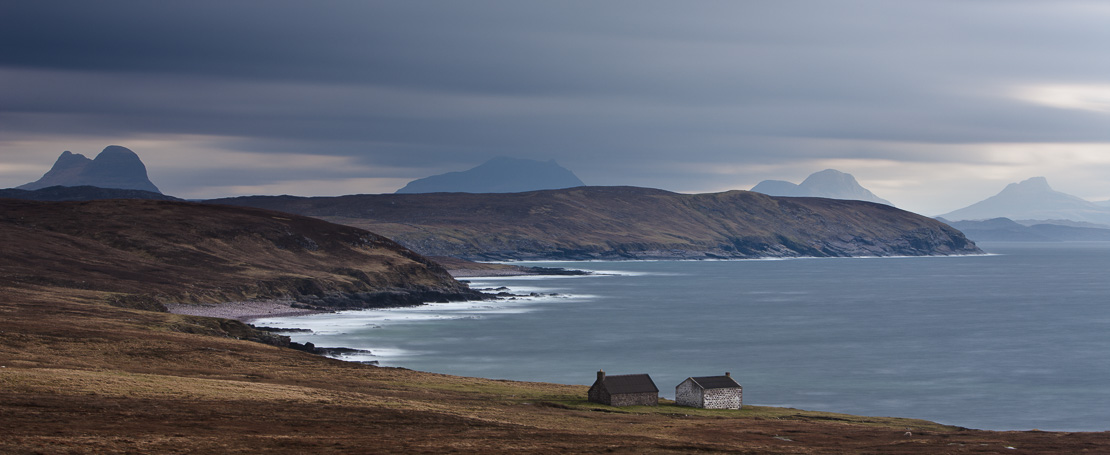 two cottages on the shore at Stoer, with the peaks of Suilven, Cul More, Cul Beag & Stac Polaidh beyond, Assynt, Sutherland, Scotland