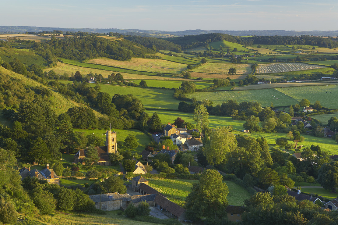 the rolling countryside of the Somerset/Dorset border with the village of Corton Denham, Somerset, England, UK.