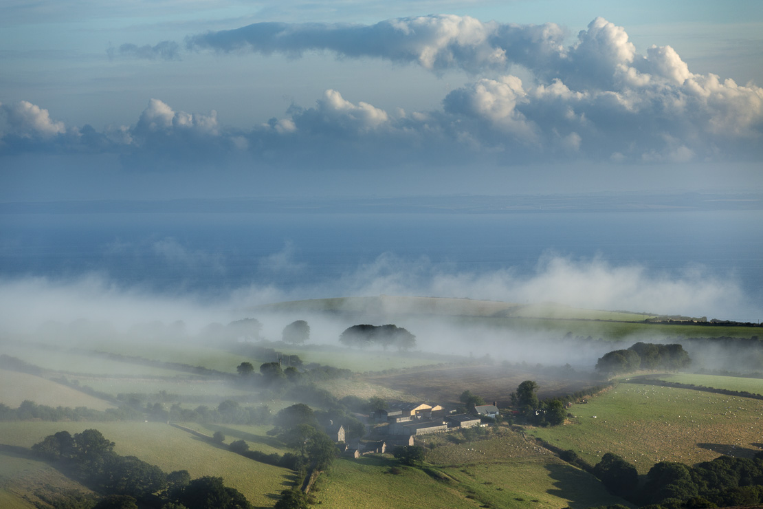 dawn mist on Porlock Hill, with the Bristol Channel and Wales beyond, Exmoor, Somerset, England, UK