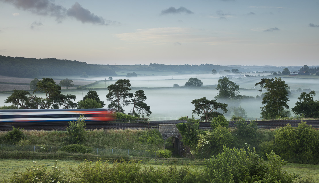 the London Waterloo to Exeter train passing Milborne Wick on a misty summer's morning, Somerset, England, UK