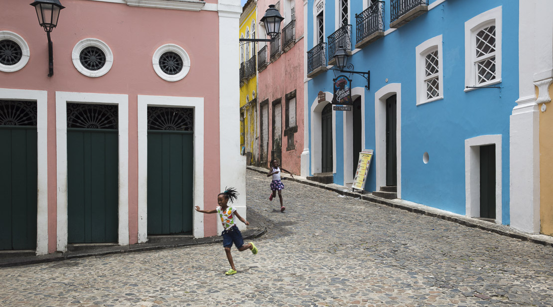 two girls running through the Pelourinho in the old town of Salvador, Bahia. Brazil