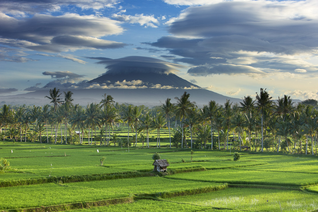 a dramatic sky over the volcanic peak of Gunung Agung and the rice fields, near Ubud, Bali, Indonesia