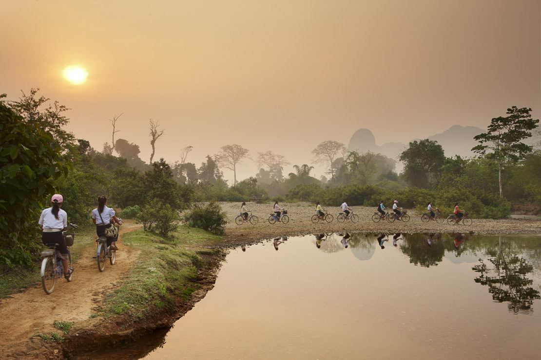 cyclists at dawn, rush hour in the countryside near Vang Vieng, Laos