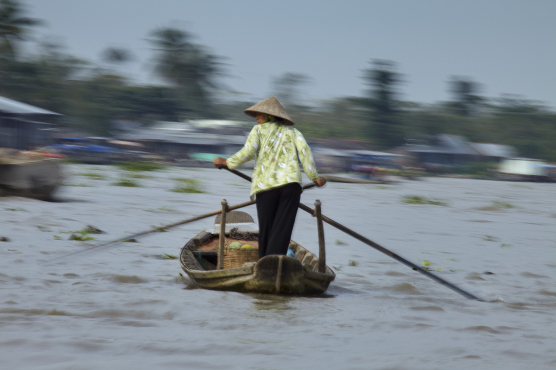 a woman rowing a boat on the Mekong River nr Can Tho, Vietnam