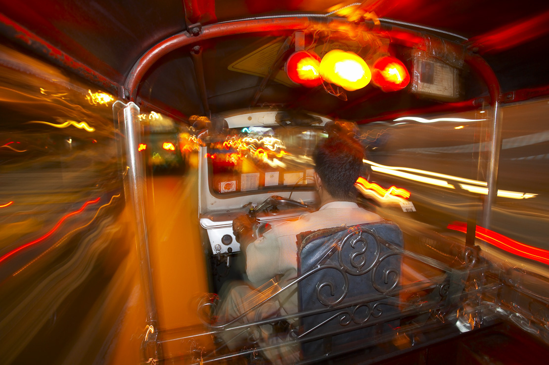 in the back of a tuk tuk at night at speed on the streets of Bangkok, Thailand