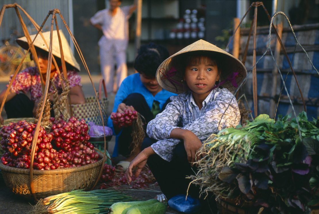 a young girl selling vegetables at a street market, Ben Tre, in the Mekong delta, Vietnam